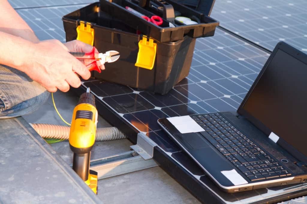 electrician at work with an electric panel with photovoltaic panels