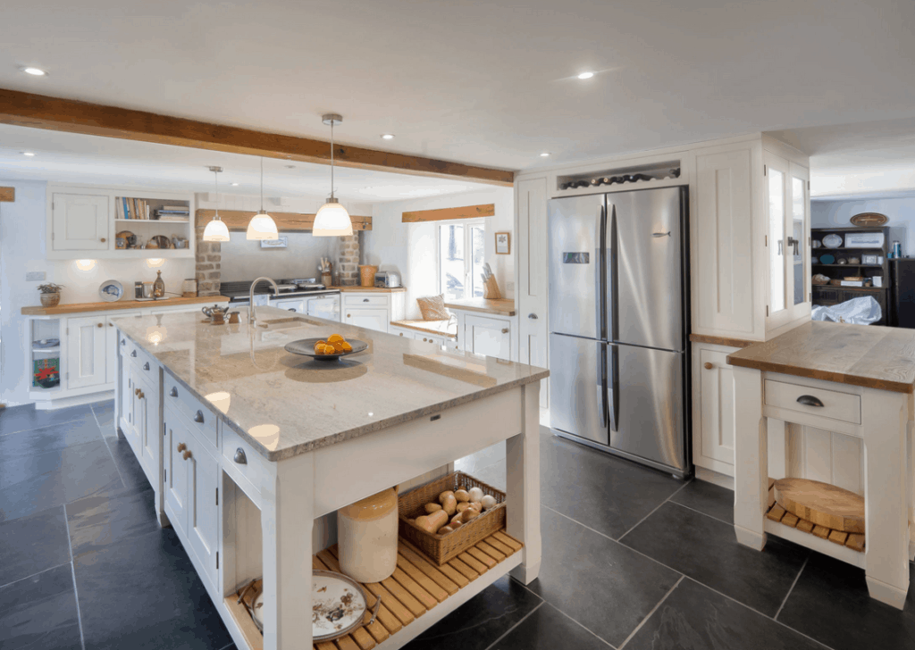 open plan farmhouse kitchen in white and wood with slate floor